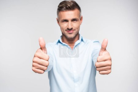 smiling adult man in shirt showing thumbs up and looking at camera isolated on white