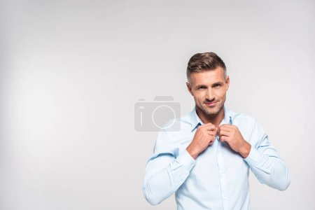handsome adult man buttoning shirt isolated on white