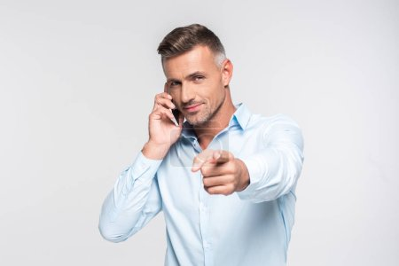 handsome adult man talking by phone and pointing at camera isolated on white