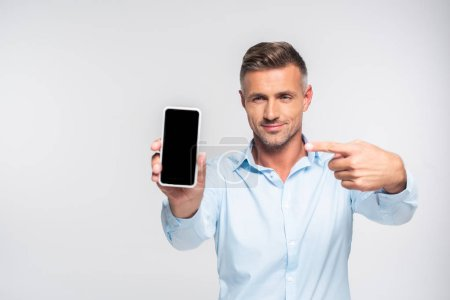 handsome adult man pointing at blank screen of smartphone isolated on white