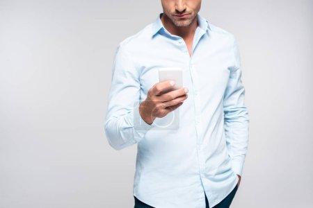 Photo pour Plan recadré de bel homme adulte en utilisant smartphone isolé sur blanc - image libre de droit