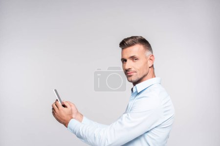 side view of handsome adult man in shirt using smartphone and looking at camera isolated on white