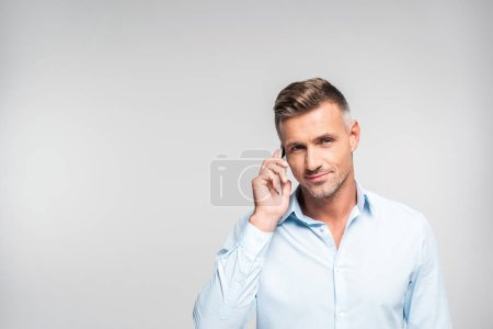 Photo for Handsome adult man talking by phone and looking at camera isolated on white - Royalty Free Image