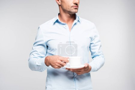 cropped shot of handsome adult man holding cup of coffee isolated on white