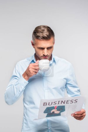 handsome adult businessman drinking coffee and reading business newspaper isolated on white