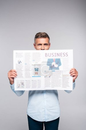 handsome adult businessman covering face with business newspaper isolated on white