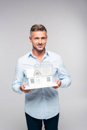 smiling adult man holding paper model of house isolated on white