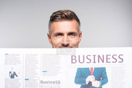 close-up shot of handsome adult businessman covering face with business newspaper isolated on white