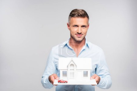 handsome adult man holding paper model of house and toy car isolated on white