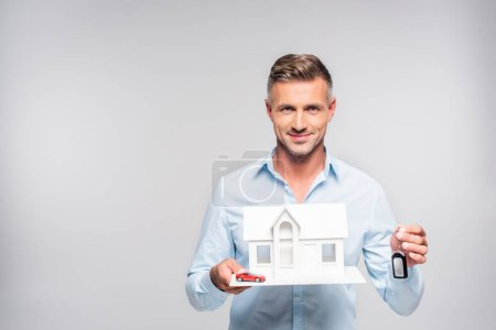 handsome adult man holding paper model of house with car alarm remote and toy car isolated on white