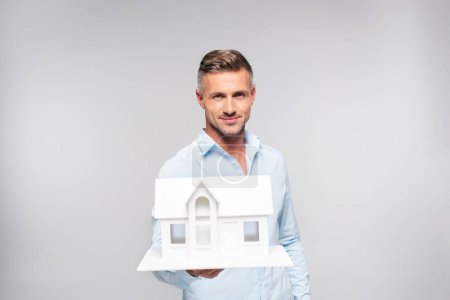 happy adult man holding paper model of house isolated on white