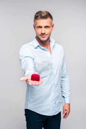 handsome adult man holding red box for proposal isolated on white