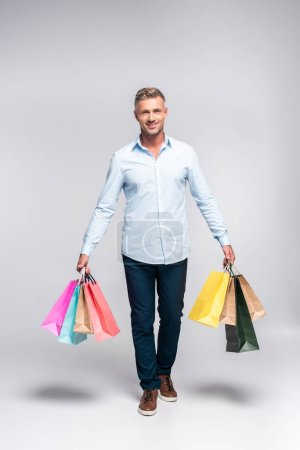 handsome adult man carrying colorful shopping bags on white