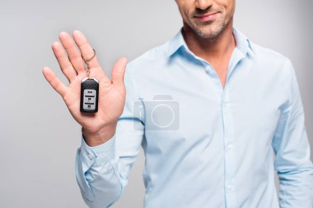 cropped shot of handsome adult man holding car alarm remote isolated on white