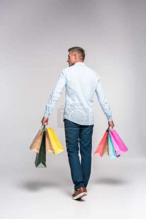 rear view of adult man carrying colorful shopping bags on white