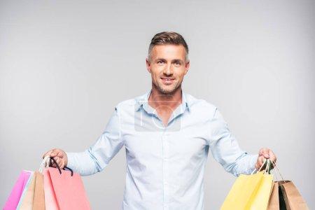 Photo pour Bel homme tenant des sacs en papier colorés et souriant à la caméra isolé sur gris - image libre de droit