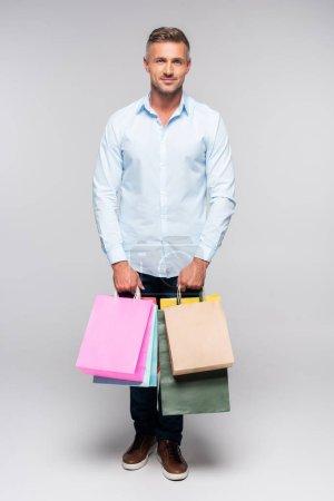 Photo pour Vue pleine longueur du bel homme tenant des sacs à provisions et regardant la caméra sur gris - image libre de droit