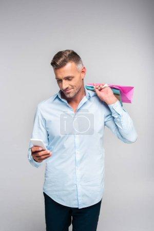 bel homme souriant tenant des sacs à provisions et à l'aide de smartphone isolé sur fond gris