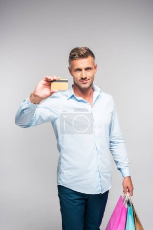 handsome man holding shopping bags and credit card isolated on grey