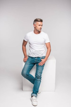 handsome man in white t-shirt and denim pants sitting and looking away on grey