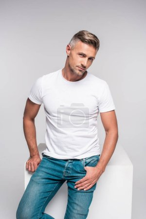 Photo for Portrait of handsome man in denim pants and white t-shirt sitting and looking at camera isolated on grey - Royalty Free Image