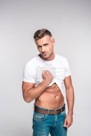 portrait of sexy man in jeans and white t-shirt looking at camera isolated on grey
