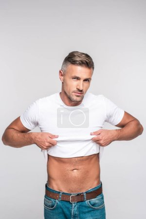 handsome man in jeans taking off white t-shirt and looking at camera isolated on grey