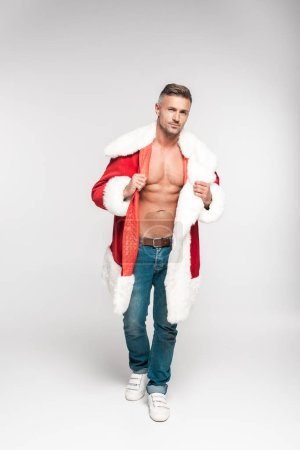 handsome muscular man wearing santa costume and looking at camera on grey