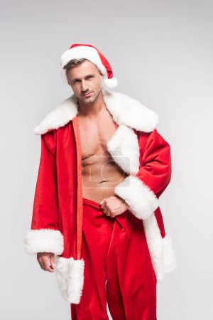 Photo for Sexy muscular man in santa costume looking at camera isolated on grey - Royalty Free Image