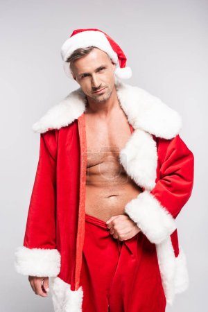 handsome muscular man in santa costume looking at camera isolated on grey