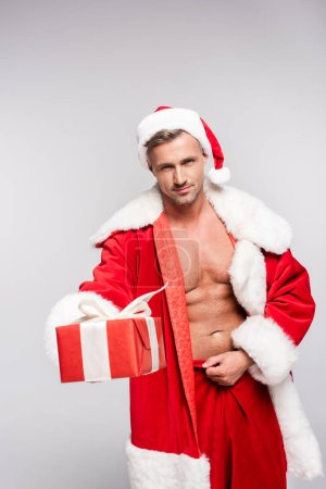 Photo for Handsome man in santa costume holding gift box and looking at camera isolated on grey - Royalty Free Image