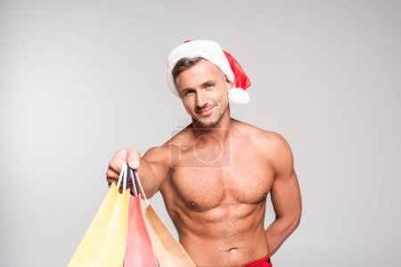 handsome muscular man in santa hat holding paper bags and smiling at camera isolated on grey