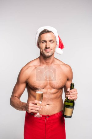 handsome shirtless man in santa hat holding glass and bottle of champagne isolated on grey