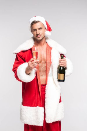 handsome sexy santa holding glass and bottle of champagne and looking at camera isolated on grey