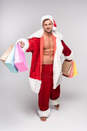 high angle view of handsome barefoot man in santa costume holding shopping bags and smiling at camera on grey