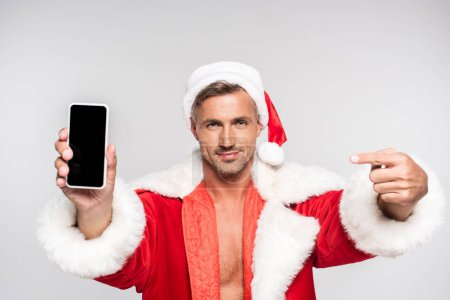 handsome smiling man in santa costume pointing with finger at smartphone with blank screen isolated on grey