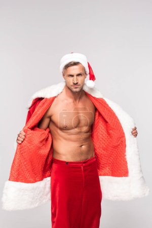 handsome sexy man wearing santa costume and looking at camera isolated on grey