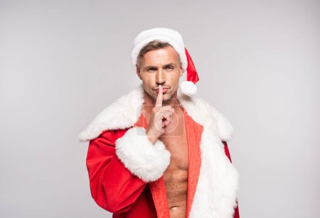 handsome man in santa costume holding finger on lips and gesturing for silence isolated on grey