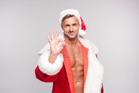 handsome happy santa showing ok sign and smiling at camera isolated on grey
