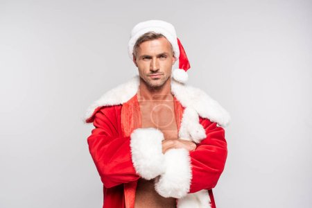 Photo for Serious handsome man in santa costume standing with crossed arms and looking at camera isolated on grey - Royalty Free Image