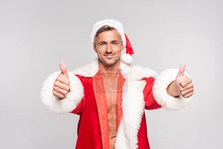 Photo for Handsome happy man in santa costume showing thumbs up and smiling at camera isolated on grey - Royalty Free Image