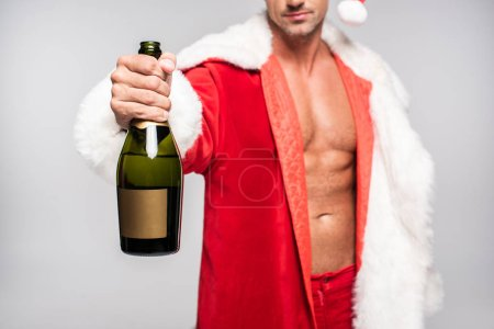 cropped shot of sexy santa holding bottle of champagne with blank label isolated on grey
