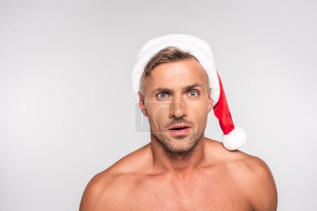 handsome shirtless surprised man in santa hat looking at camera isolated on grey