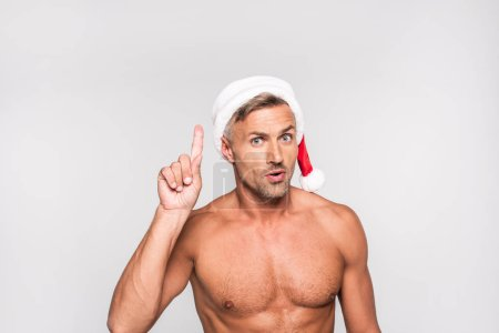 handsome shirtless man in santa hat pointing up with finger and looking at camera isolated on grey