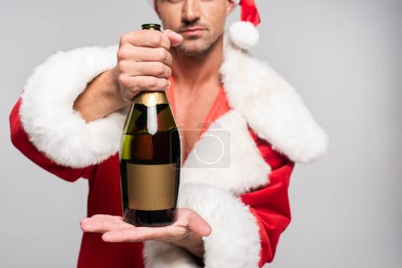 cropped shot of man in santa costume holding bottle of champagne with blank label isolated on grey