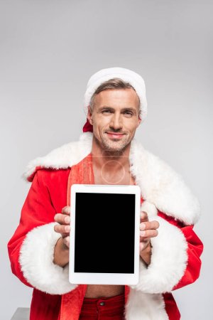 Photo for Handsome man in santa costume holding digital tablet with blank screen and smiling at camera isolated on grey - Royalty Free Image