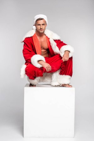 handsome man in santa costume crouching on white cube and looking at camera on grey