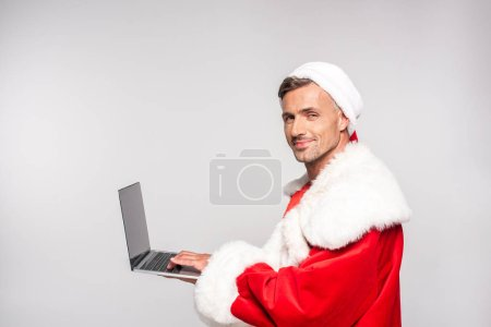 Photo for Handsome man in santa costume using laptop and smiling at camera isolated on grey - Royalty Free Image