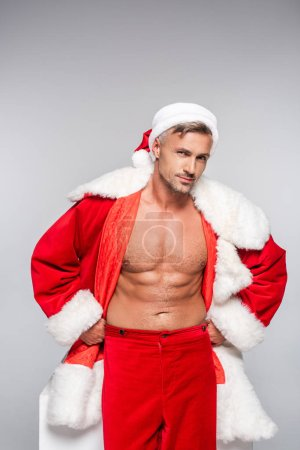 Photo for Handsome sexy santa standing with hands on hips and smiling at camera isolated on grey - Royalty Free Image