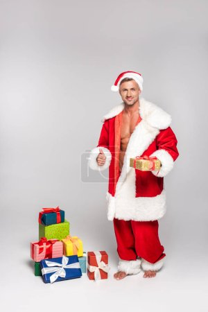 sexy man in santa costume holding christmas present and showing thumb up on grey
